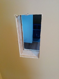 The first step was to cut a hole in the wall using a drywall saw and a couple of 2 by 4s to frame in the hole.