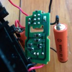 It looks like the circuit has a transistor that interrupts the circuit to the motor when there is power coming in from the wall.  When the switch is on, power comes from the batteries and the circuit is broken from the adaptor.